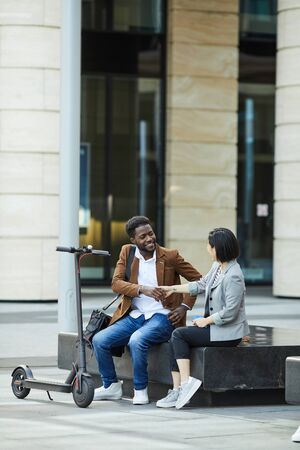 Portrait of smiling African-American man shaking hands with Asian woman while sitting on bench outdoors, copy space