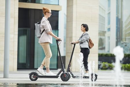 Full length portrait of modern young people commuting in city, focus on woman riding electric scooter in foreground, copy space Stock Photo - 130072105