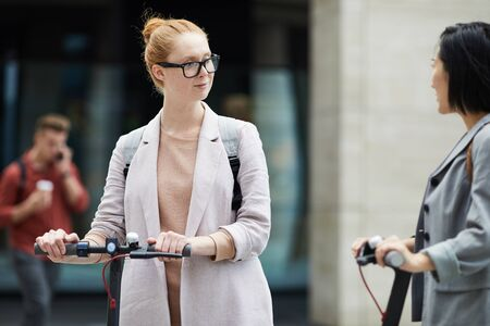 Waist up portrait of contemporary red haired woman talking to friend while riding electric scooter in urban setting, copy space Zdjęcie Seryjne