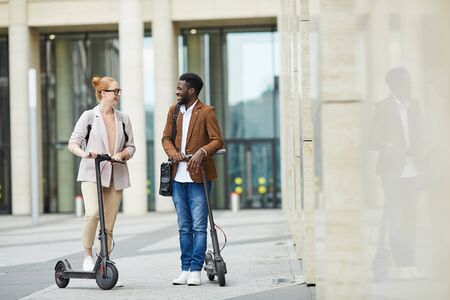 Full length portrait of mixed race young couple riding alectric scooters in city street and smiling happily, copy space
