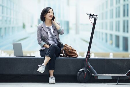 Blue-toned full length portrait of modern Asian woman speaking by smartphone sitting on bench near street fountain with electric scooter in foreground, copy space