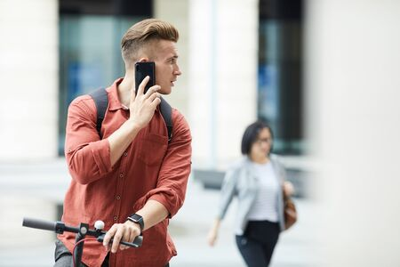 Waist up portrait of handsome young man speaking by smartphone while riding electric scooter in urban setting, copy space