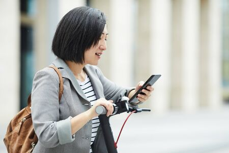 Waist up side view of modern Asian woman checking smartphone while riding electric scooter in urban setting, copy space