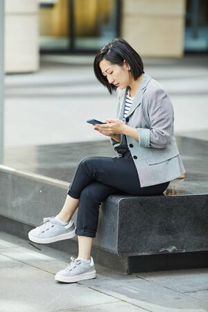 Full length side view of modern Asian woman using smartphone while sitting on bench outdoors in urbnan setting, copy space