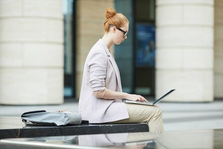 Side view poirtrait of conteporary young woman wearing glasses using laptop while working outdoors in urban setting, copy space 写真素材