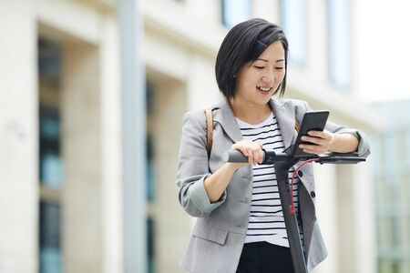 Waist up portrait of smiling Asian woman checking messages via smartphone while riding electric scooter in urban setting, copy space