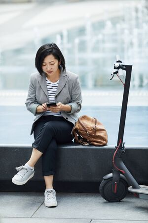 Full length portrait of modern Asian woman using smartphone sitting by street fountain with electric scooter in foreground