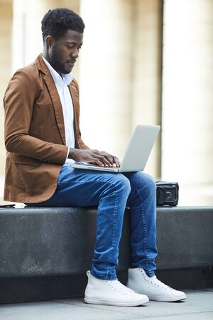 Full length side view of young African-American man using laptop outdoors while working on freelance project in urban setting, copy space Фото со стока