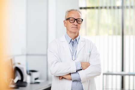 Portrait of friendly senior doctor wearing glasses looking at camera while posing in office standing with arms crossed, copy space Фото со стока