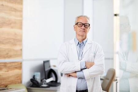 Waist up portrait of senior doctor wearing glasses looking at camera while standing with arms crossed in office of modern clinic, copy space