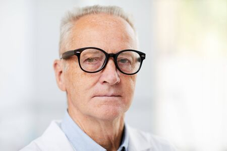 Head and shoulders portrait of white haired senior doctor wearing glasses and looking at camera while posing in office, copy space