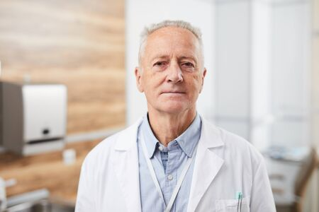 Waist up portrait of senior doctor smiling calmly looking at camera while posing in office of modern clinic, copy space