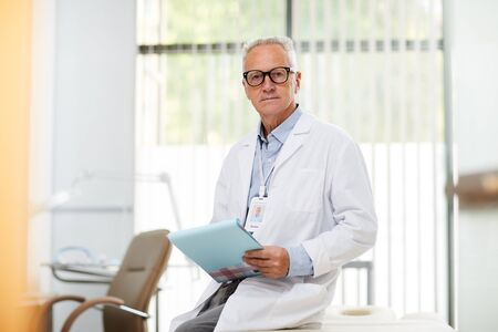 Waist up portrait of professional senior medic holding clipboard and looking at camera while taking notes standing in office of modern clinic, copy space