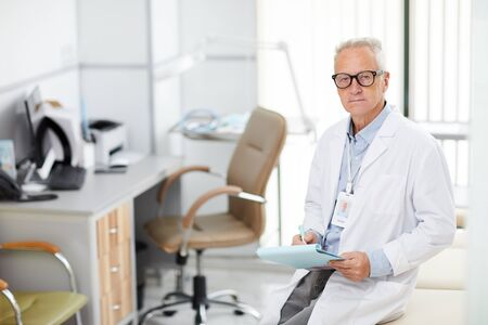 High angle portrait of professional senior medic holding clipboard and looking at camera while taking notes standing in office of modern clinic, copy space