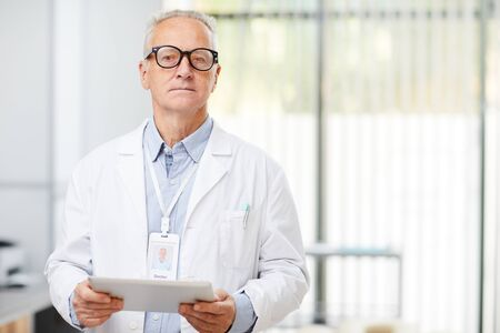 Waist up portrait of senior doctor holding digital tablet and looking at camera while standing in office of modern clinic Stock Photo
