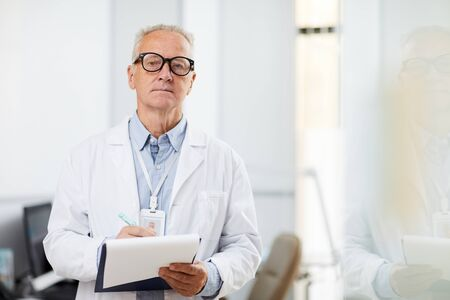 Waist up portrait of senior doctor holding clipboard and looking away pensively while taking notes standing in office, copy space