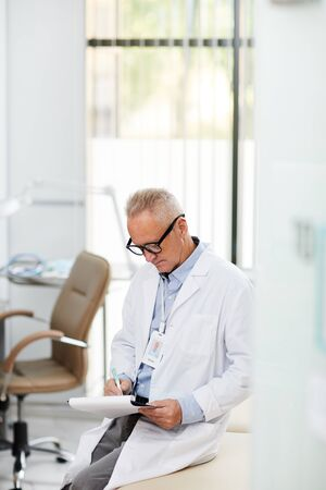 High angle portrait of senior doctor writing on clipboard during consultation in office of modern clinic, copy space 스톡 콘텐츠