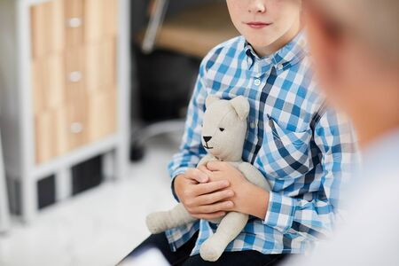 Close up of unrecognizable boy hugging bear toy while talking to doctor during consultation in child healthcare clinic, copy space