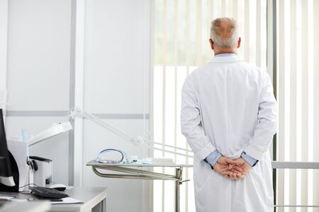 Back view portrait of pensive senior doctor looking at window while standing in office of modern clinic, copy space