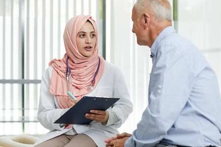 Portrait of young Arab woman working as doctor in medical clinic and talking to senior patient filling in form on clipboard, copy space