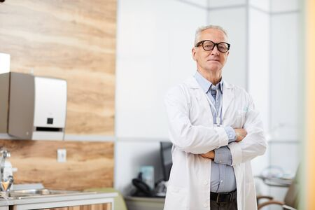 Portrait of confident senior doctor looking at camera while posing standing in office of modern clinic, copy space Stock Photo