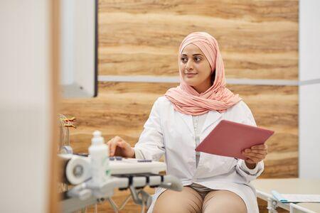 Porträt einer jungen arabischen Frau, die elektronische Maschinen verwendet, während sie als Krankenschwester in einer medizinischen Klinik arbeitet, Kopierraum