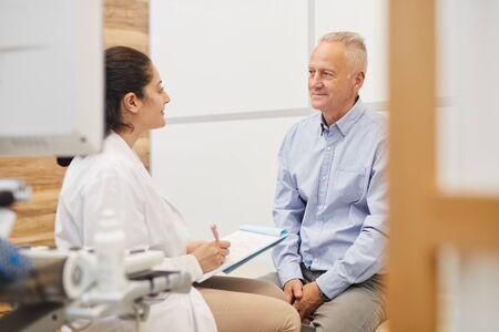 Porträt einer freundlichen Ärztin, die in die Zwischenablage schreibt, während sie einen älteren Patienten in einer medizinischen Klinik untersucht, Platz kopieren