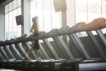 Wide angle back view portrait of young woman running on treadmill alone in empty gym, copy space