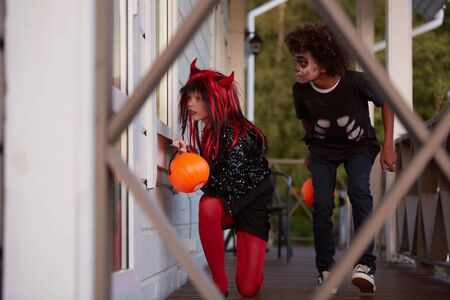 Portrait of two sneaky kids hiding outside house while playing games on Halloween, copy space