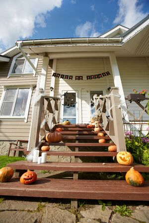 Low angle view at Halloween decorations on front lawn and porch of house in suburban are, copy space