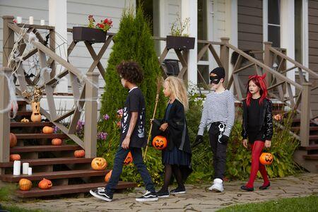 Grupo multiétnico de niños engañando o tratando juntos y vistiendo disfraces de Halloween, espacio de copia