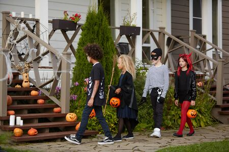 Multi-ethnic group of children trick or treating together and wearing Halloween costumes, copy space