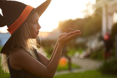 Side view portrait of cute little witch holding frog while playing outdoors in Halloween, copy space