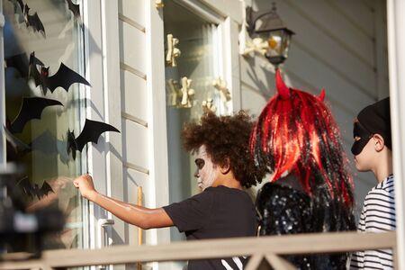 Grupo multiétnico de niños que hacen truco o trato juntos y tocan puertas, todos vestidos con disfraces de Halloween