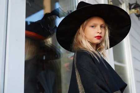 Side view portrait of cute little witch looking at camera while posing outdoors in Halloween season, copy space Banco de Imagens