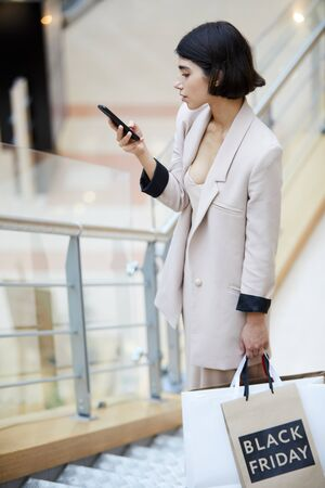 High angle portrait of beautiful young woman enjoying shopping spree on sale standing on stairs in mall and texting while holding bags with BLACK FRIDAY