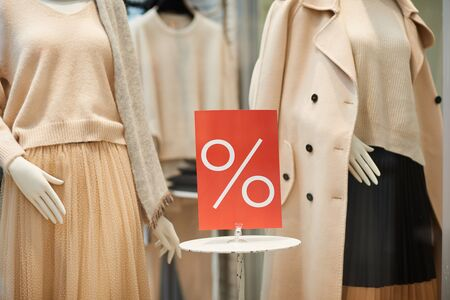 Close up of red SALE percent sign on window display with autumn clothes in shopping mall, copy space