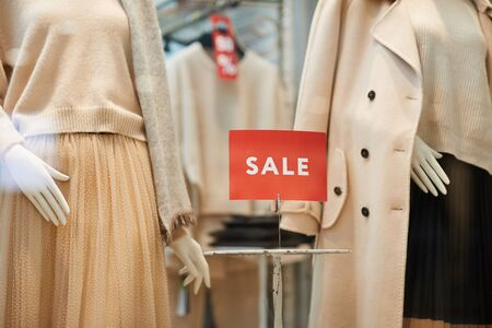 Closeup of red SALE sign on window display with autumn clothes in shopping mall, copy space Фото со стока