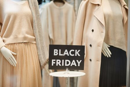 Close up of Black Friday sale sign on window display with autumn clothes in shopping mall, copy space Фото со стока