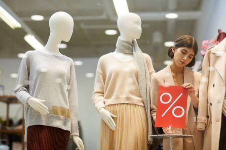 Retrato de hermosa vendedora que fija el cartel de venta rojo y maniquíes vestidos con ropa de otoño mientras configura el escaparate en la tienda, espacio de copia Foto de archivo