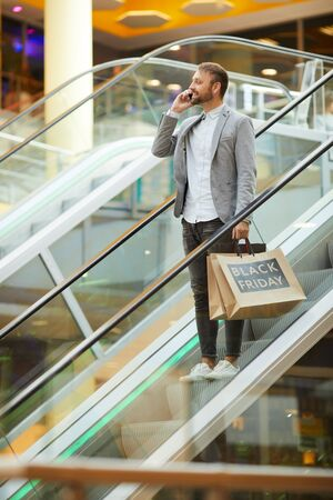 Portrait of fashionable man holding shopping bags with Black Friday inscription while speaking by phone standing on escalator in mall, copy space