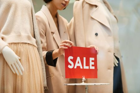 Closeup of saleswoman fixing red SALE sign and mannequins dressed Autumn clothes while setting up window display in store, copy space