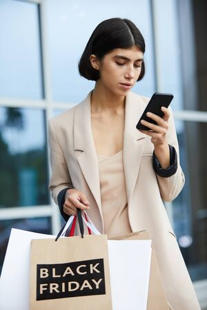 Waist up portrait of elegant young woman holding shopping bags with Black Friday and using smartphone on the go while leaving mall in sale season