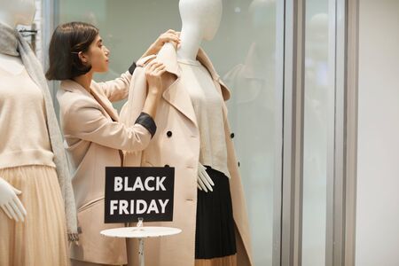 Portrait of beautiful saleswoman dressing mannequins in Autumn clothes while setting up window display for Black Friday , copy space