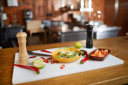 Background image of hot Asian dish and cooking ingredients set on wooden table in restaurant kitchen Reklamní fotografie