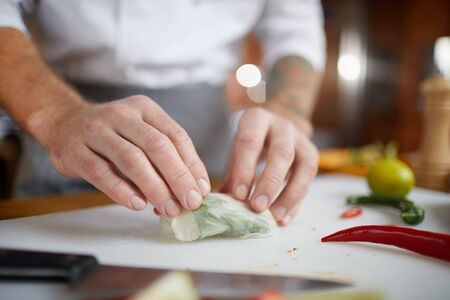 Close up of professional chef wrapping vegetable rolls while cooking Asian food in restaurant kitchen, copy space