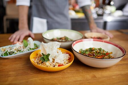 Background image of several Asian dishes set on wooden table in cafe or restaurant, copy space