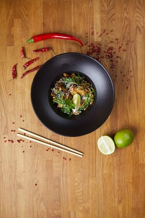 Above view background of beautiful Asian dish in wok bowl set on wooden table decorated with hot red pepper and lime, copy space