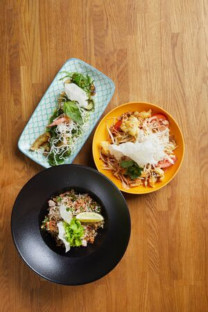 Above view background of three Asian dishes set on wooden table in cafe or restaurant, copy space
