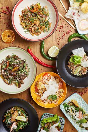 Vista anterior de fondo de hermosos platos asiáticos en mesa de madera decorada con ají y limón, espacio de copia Foto de archivo